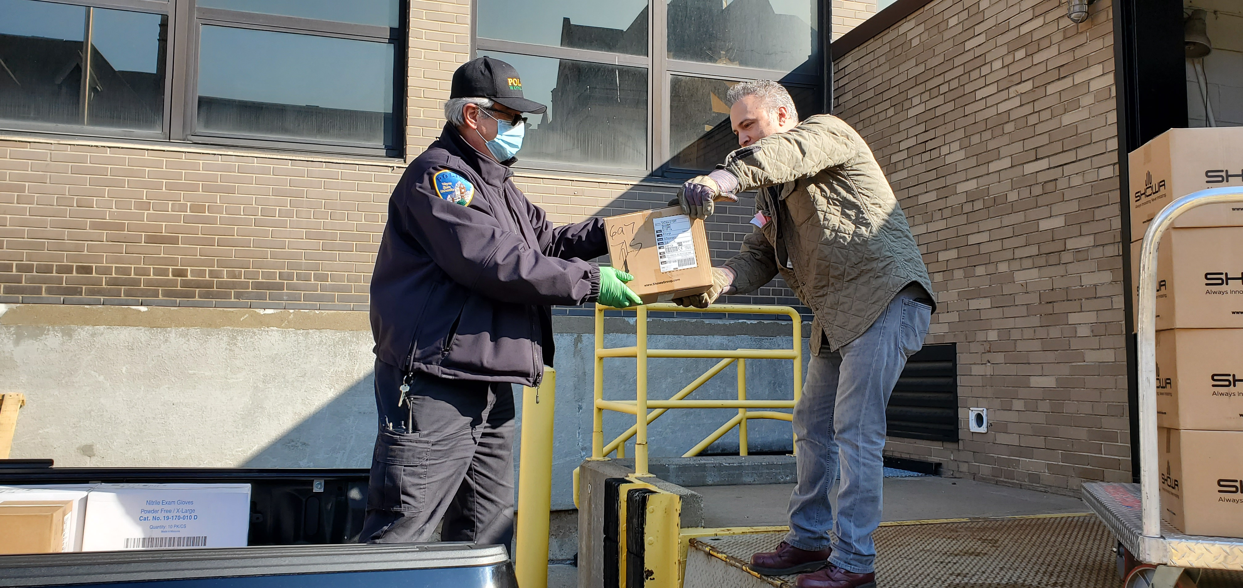 Storeskeeper Jason Parizon hands off PPE to the Wayne State Police