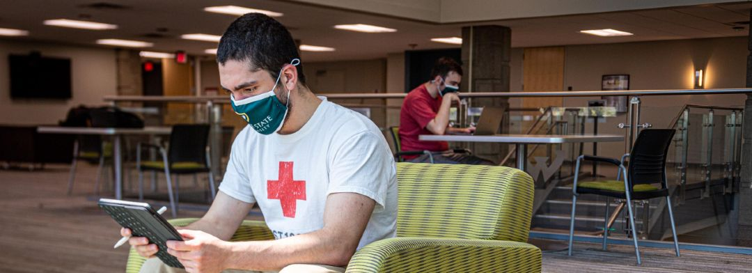 Masked student studies in the Student Center Building